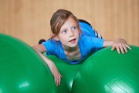 Mädchen auf grünen Gymnastikbällen