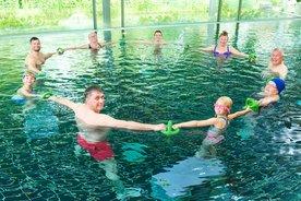Mehrere Menschen mit Sportgeräten im Schwimmbecken