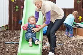 Frau mit Kind auf der Rutsche